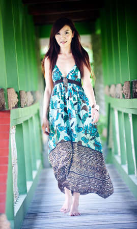 A beautiful asian woman in a dress walking down a corridor photo