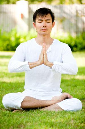 An attractive asian man meditating outdoors in a garden Stock Photo - 6013141