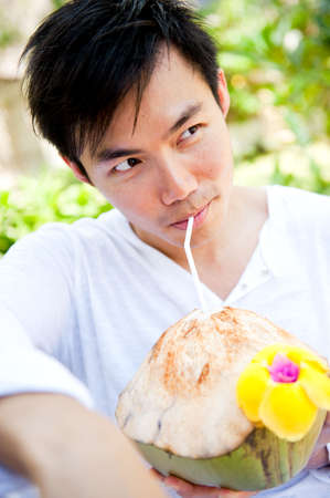 An attractive asian man drinking from a coconut outdoors Stock Photo - 6013135