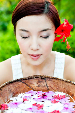 An attractive asian woman with a bowl of flowers outdoors photo