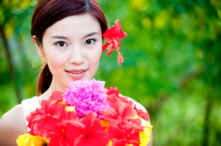 A beautiful asian woman holding a bouquet of bright and colourful flowers outdoors photo