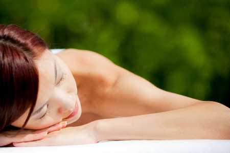 A beautiful asian woman lying down on a massage table outdoors in the sun