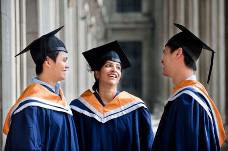 Three young graduates wearing graduation attire chatting in a hallway photo