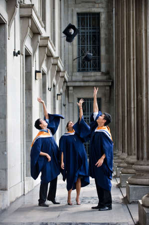A group of graduates toss their mortar boards into the air in a hallway photo