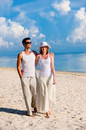 suntanning: A couple walking along a sandy beach Stock Photo