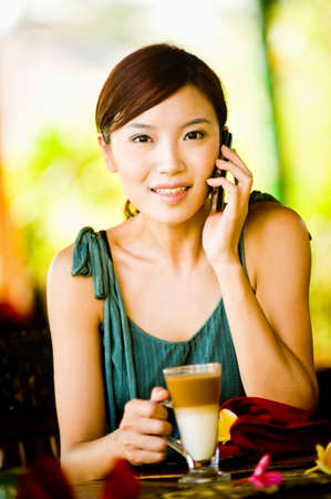 A young woman drinking coffee while talking on the phone photo