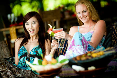 Two young attractive women having lunch and drinks at a restaurant photo
