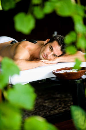 A good looking man lying on a massage bed with hot stones on his back photo