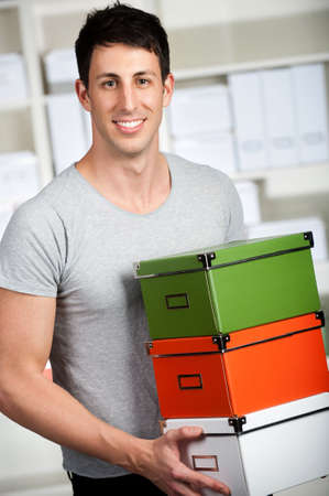 good looking man: A good looking man carrying stacks of cardboard boxes at home Stock Photo