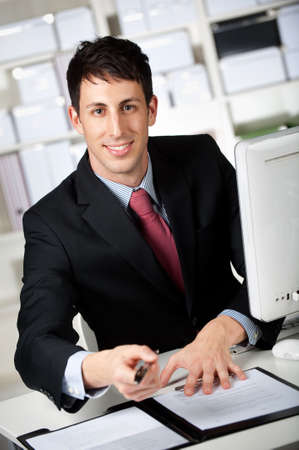 A good looking businessman with a pen and a contract in his office photo