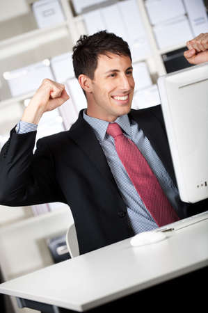 news online: A good looking businessman in the office receives good news online and pumps his fists in the air