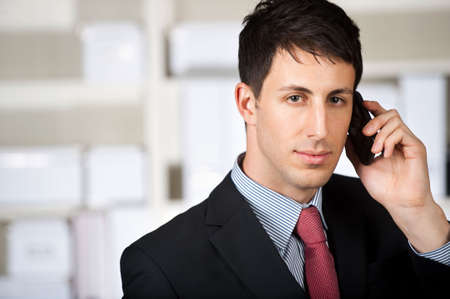 A good looking businessman using his mobile phone in the office Stock Photo - 6048854