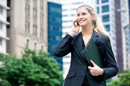 A young and attractive businesswoman using her mobile phone and holding a file under her arm photo