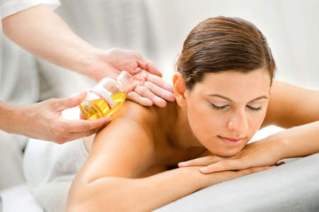 aromatherapy oils: An attractive caucasian woman getting massaged in a spa Stock Photo