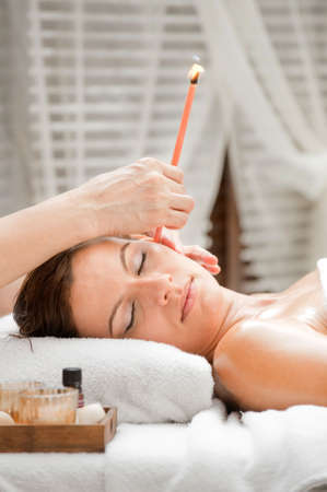 Ear candling being carried out on an attractive caucasian woman in a spa photo