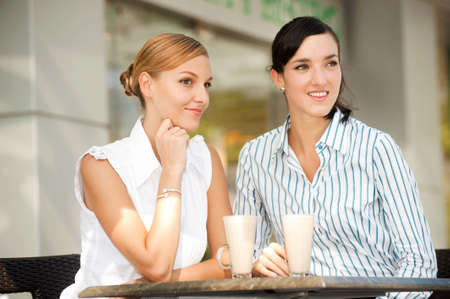 Two attractive businesswomen chatting over coffee photo