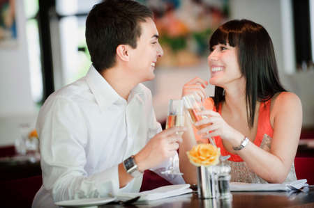 An attractive young couple toasting with white wine in a restaurant photo