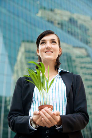 An attractive businesswoman cupping a plant in her hands against city backdrop