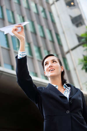 An attractive young businesswoman holding a paper plane against city backdrop Stock Photo