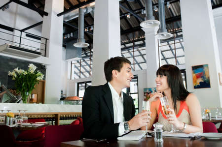 An attractive young couple toasting with white wine in a restaurant