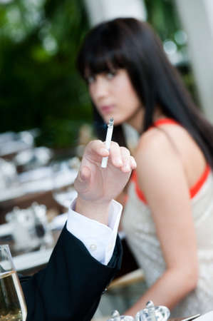 A young and attractive woman irritated by the smoke from a cigarette at an outdoor dining area photo