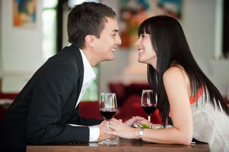 couple holding hands: A young and attractive couple holding hands and about to kiss over their dinner in an indoor restaurant Stock Photo