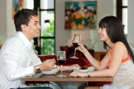 A young and attractive couple dining together in an indoor restaurant