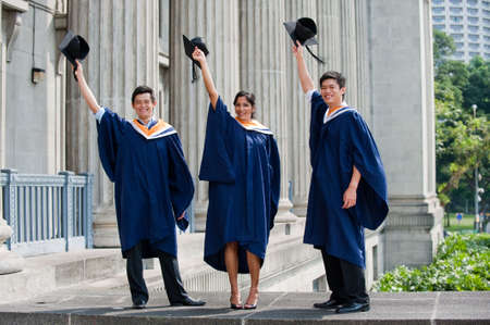 A group of graduates toss their mortar boards into the air