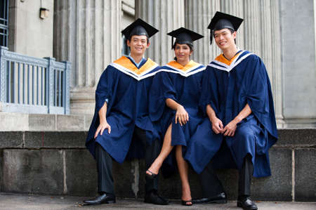 Three young graduates standing outdoors in graduation attire Stock Photo