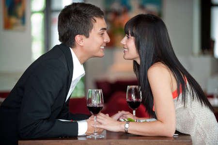 over eating: A young and attractive couple holding hands and about to kiss over their dinner in an indoor restaurant Stock Photo