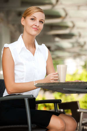 An attractive young businesswoman talking on the phone while having coffee photo