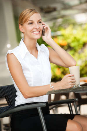 An attractive young businesswoman talking on the phone while having coffee Stock Photo