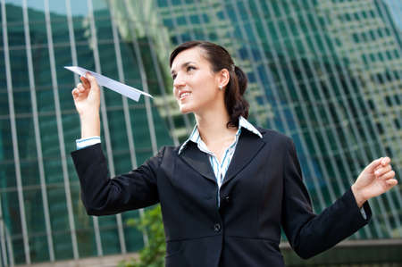 An attractive young businesswoman holding a paper plane against city backdrop photo