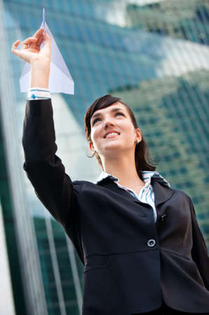 An attractive young businesswoman holding a paper plane against city backdrop Stock Photo - 6208865
