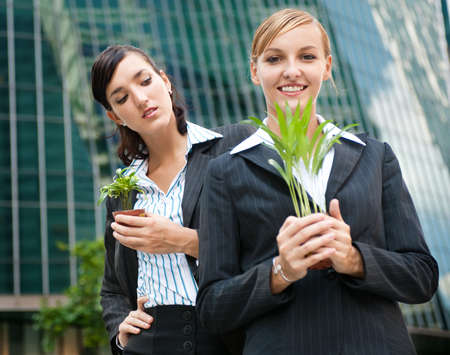 envy: Two competitive businesswomen cupping their plants in their hands Stock Photo