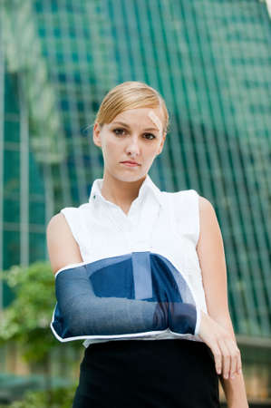 A young businesswoman with injured arm and band-aid standing in the city photo