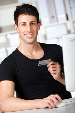 good looking man: A good looking man doing an online payment at home using his credit card Stock Photo