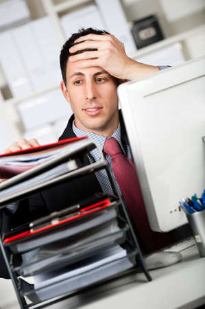 cansancio: Un hombre de negocios atractivo con una pesada carga de trabajo en su Oficina