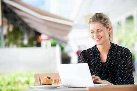 A young attractive caucasian woman uses a laptop outdoors at a cafeteria photo