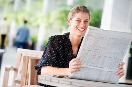 read news: A young attractive woman reading newspapers at a cafeteria