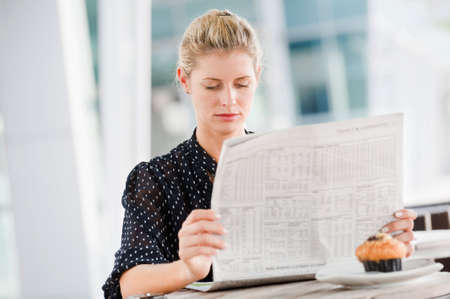 A young attractive woman reading newspapers at a cafeteria Stock Photo - 6309549