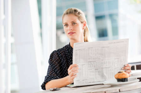A young attractive woman reading newspapers at a cafeteria Stock Photo - 6309543