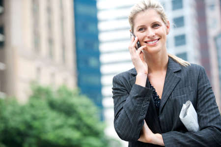 A young and attractive businesswoman using her phone with newspapers under her arm Stock Photo - 6309564