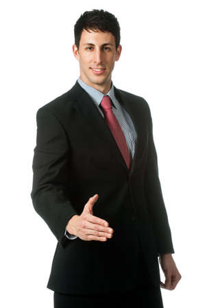 A good looking businessman extending out his hand for a handshake against white background