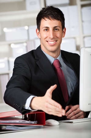 A good looking businessman extending out his hand for a handshake over his office table Stock Photo