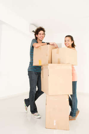 A young and attractive couple with boxes of belongings in their new home photo