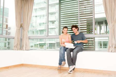 A young and attractive couple using laptop by the windows in their new home photo