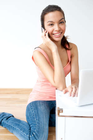 A young and attractive asian woman talking on the phone and using her laptop in her new home Stock Photo - 6338209