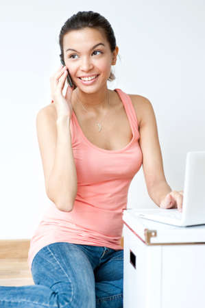 A young and attractive asian woman talking on the phone and using her laptop in her new home photo