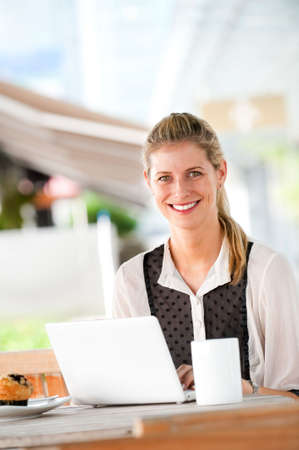 A young attractive caucasian woman uses a laptop outdoors at a cafeteria Stock Photo - 6338203